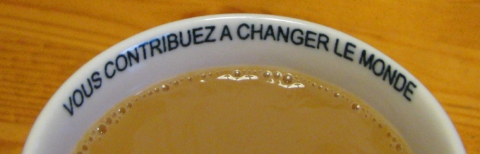 Vous contribuez a changez le monde - printed just inside the rim of a porcelain coffee cup filled with Fair trade coffee