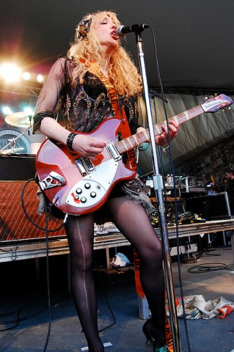 Courtney Love in concert, playing her guitar; with an artistic run in her black stocking