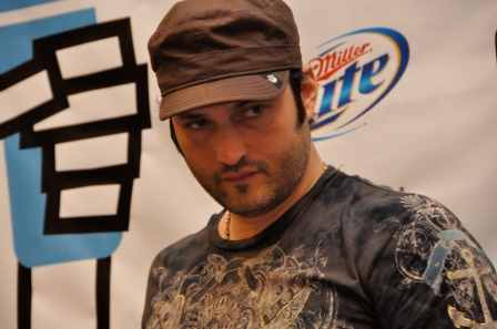 film maker Robert Rodriguez in stubble, camo & a baseball cap at a press function