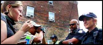 L - R Bubble blowing female protester stands in front of Female officer,  Male camera wielding protester stands directly in front of Officer Adam Josephs