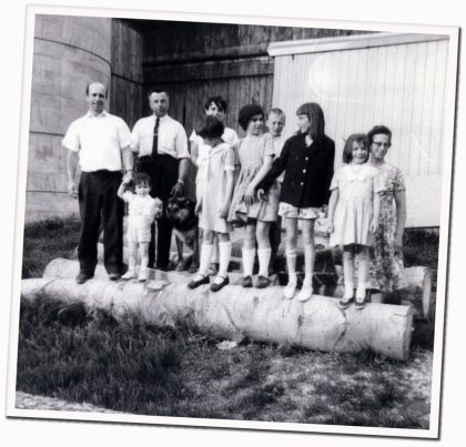 black and white snapshot of the two families intermingled, standing on giant logs in front of the barn