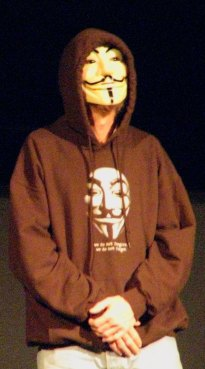 Onstage: panelist wearing Guy Fawkes mask