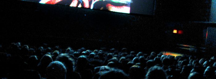 packed theatre watches the film