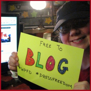 "Laurel holds a ""Free to Blog"" sign with the hashtags #WPFD and #PressFreedom"